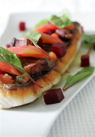 Seared sea bass with tomato confit and red onion and bacon vinaigrette
